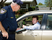 Police - Drunk Driver Guilty. Police officer pulling over a drunk driver.  The driver is holding a beer and looking embarassed Royalty Free Stock Photos