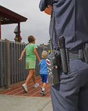 Police Guardian watching. Children in play area in park well policeman watches over them royalty free stock image