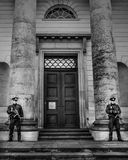 Police guarding a building. Black and white shot of two uniformed policemen holding sub-machine guns while guarding the doorway at the pillars of a large Stock Photos