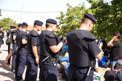 Police guarding the waiting line of Refugees in Tovarnik Stock Images