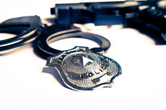 Police gun, badge and handcuffs. Gun, handcuffs and police badge isolated Stock Image
