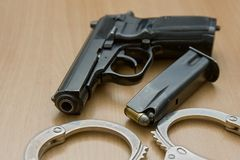 Police gun with the cartridge with the bullets and hand cuffs Royalty Free Stock Photo