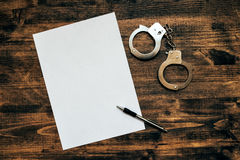 Police handcuffs and blank paper on investigator detective's wor. K desk, concept of law and crime royalty free stock photo
