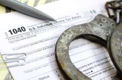 Police handcuffs lie on the tax form 1040. The concept of proble. Ms with the law in the aftermath of non-payment of taxes Royalty Free Stock Photography