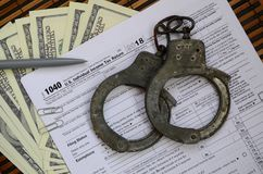 Police handcuffs lie on the tax form 1040. The concept of proble. Ms with the law in the aftermath of non-payment of taxes Royalty Free Stock Images