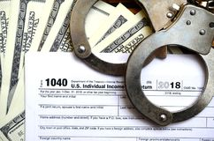 Police handcuffs lie on the tax form 1040. The concept of proble. Ms with the law in the aftermath of non-payment of taxes Stock Images