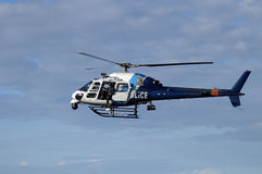 Police helicopter. Blue and white police helicopter flying in the sky, door is open and a police man is looking down Royalty Free Stock Image
