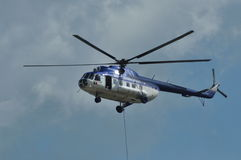 Police helicopter in action with hanging people Stock Photography