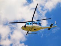 Police helicopter in action, propellers are turning and the machine is flying. Blue sky in background royalty free stock photography