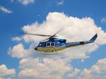 Police helicopter in action, propellers are turning and the machine is flying. Blue sky in background stock image
