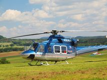 Police helicopter in action, propellers are turning and the machine is ready to fly. Blue sky in background royalty free stock photography