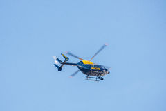 Police helicopter flying against a clear blue sky Royalty Free Stock Photography