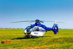 Police helicopter on a green grass field preparing to take off Stock Photography
