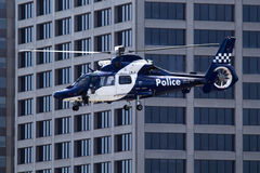 Police Helicopter. S flying alongside a building in an urban area Stock Photography
