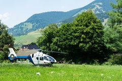 A police helicopter landed in a mountainous village in the field stock images