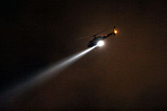 Police Helicopter with searchlight at night. A LAPD helicopter searches for a suspect with a bright search light in Los Angeles stock image