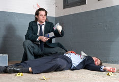 Police inspector. Discovering a controlled substance during his murder investigation Stock Photography