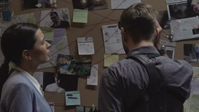 Police inspectors analyzing crime board information and giving five, solution. Stock footage stock footage