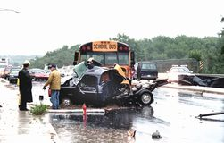 Police investigate an auto accident involving a school bus. Police examine an auto accident involving a schoolbus during a rainstorm in College Park, Maryland stock photo