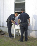 Police investigating burglary. Police woman dusting for finger prints at crime scene, someone broke into offices Royalty Free Stock Image