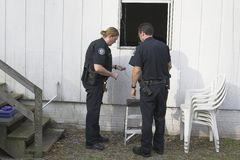 Police investigating burglary. Police woman dusting for finger prints at crime scene, found telephone alarm wires cut Royalty Free Stock Images