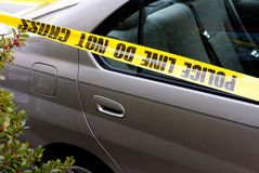 Police Line. Tape draped across a car at a crime scene Stock Image