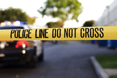 Police line. Yellow police tape at a crime scene with a police car in the background Royalty Free Stock Image