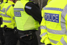 Police line. Police officers form a cordon on a wet spring day Royalty Free Stock Images