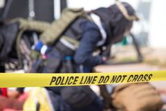 Police line do no cross with blurred law enforcement background. Police line do no cross with blurred law enforcement searching background in academy training stock image