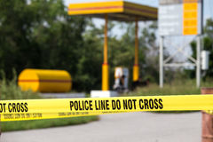 police line do no cross with gas station background in crime scene stock photo