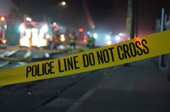 Police Line: Do Not Cross. Yellow tape warning people to stay away from a crime scene in the city at night Stock Photos