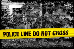 Police Line Do Not Cross Tape at Crime Scene House. Police line do not cross yellow warning tape in front of grunge black and white house of horror cordoned off Royalty Free Stock Photography
