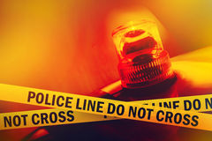 Police Line Do Not Cross. Yellow Headband Tape and Orange flashing and revolving light. Murder Scene Police Ribbon Stock Image