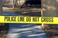 Yellow caution tape with police line do not cross. Police line do not cross yellow tape in front of crime scene royalty free stock photo