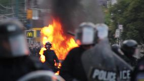 Police line with riot gear holds back crowd with car fire - HD 1080p. Riot police officers with helmet shield baton visors stand and guard a perimeter with a