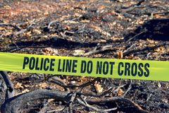 Police line tape in front of burn area. Yellow tape POLICE LINE DO NOT CROSS in front of burned out structure debri flattened to the ground in the wild fire that Royalty Free Stock Photography