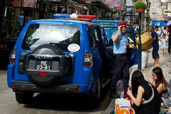 Police in Macau. Police officer stepping out of a patrol vehicle on a crowded street Royalty Free Stock Image