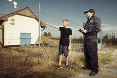 Police man questioning a teenage boy in fields Stock Photos