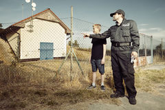 Police man questioning a teenage boy in fields Stock Photography