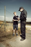 Police man questioning a teenage boy in fields Royalty Free Stock Images