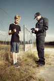 Police man questioning a teenage boy Royalty Free Stock Image
