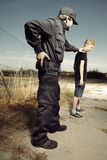 Police man taking a teenager to handcuffs Royalty Free Stock Images