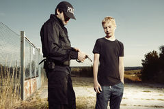 Police man taking a teenager to handcuffs Royalty Free Stock Photography