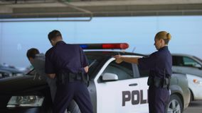 Police mates arresting dangerous criminal, wearing handcuffs and aiming gun. Stock footage stock video