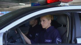 Police mates getting into patrol car ready to drive to crime scene, public order. Stock footage stock video