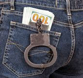 Police metal handcuffs and american currency in jeans pocke Stock Images