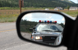 Police in the Mirror. Police in the sideview mirror pulling over car Stock Image