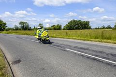 Police motorcycle outrider riding at speed through British countryside royalty free stock photography