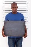 Police mug shot. Young african man holding a black board police mug shot Royalty Free Stock Photography