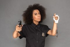 Police. Mulatto woman standing isolated on grey pointing camera with gun holding handcuffs cool stock image